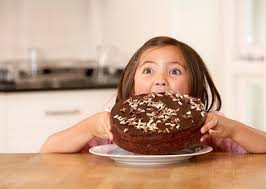 Little Girl about to Chomp Down on Big Chocolate Cake