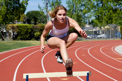 Woman Jumping a Track Hurdle