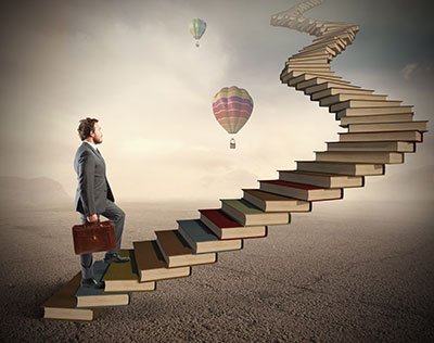 Businessman Climbing a Staircase of Books