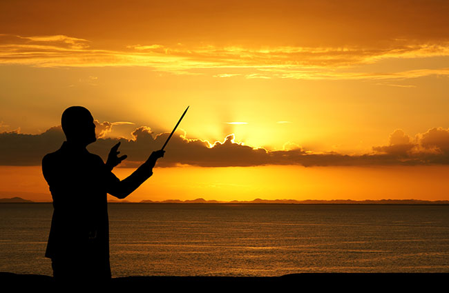 Music Conductor Conducting the Sunset over Ocean