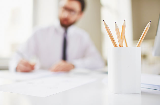 Man Writing with Pencils in Foreground