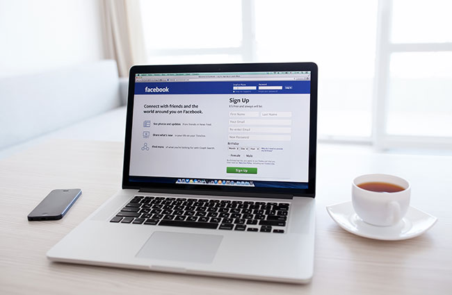 Facebook on Laptop with Coffee